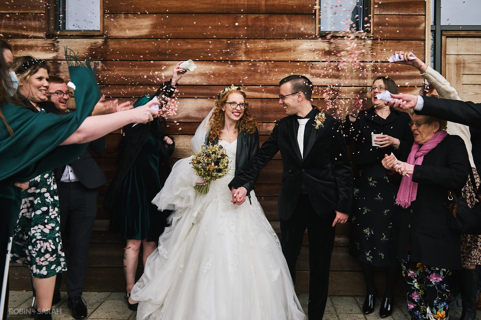Alternative bride and groom happy and smiling as wedding guests throw confetti