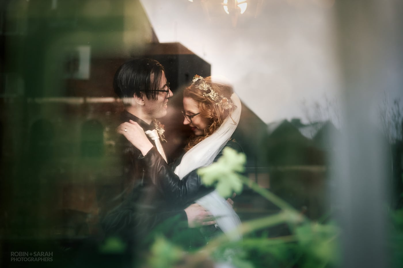 View through window of bride and groom hugging at The Chimney House, with reflects of buildings