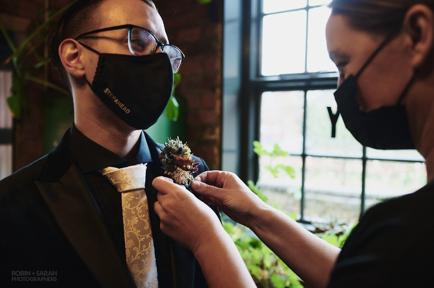 Groom has buttonhole flower fixed by staff