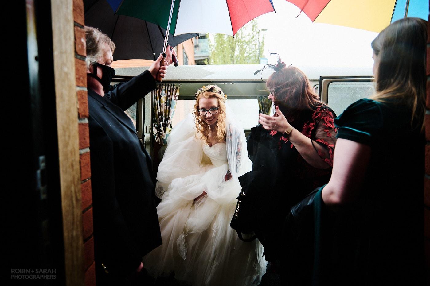 Bride arrives for wedding in camper van as guests hold up umbrellas for her