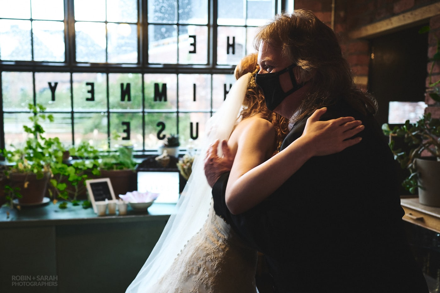 Bride hugs dad as she arrives for wedding at The Chimney House