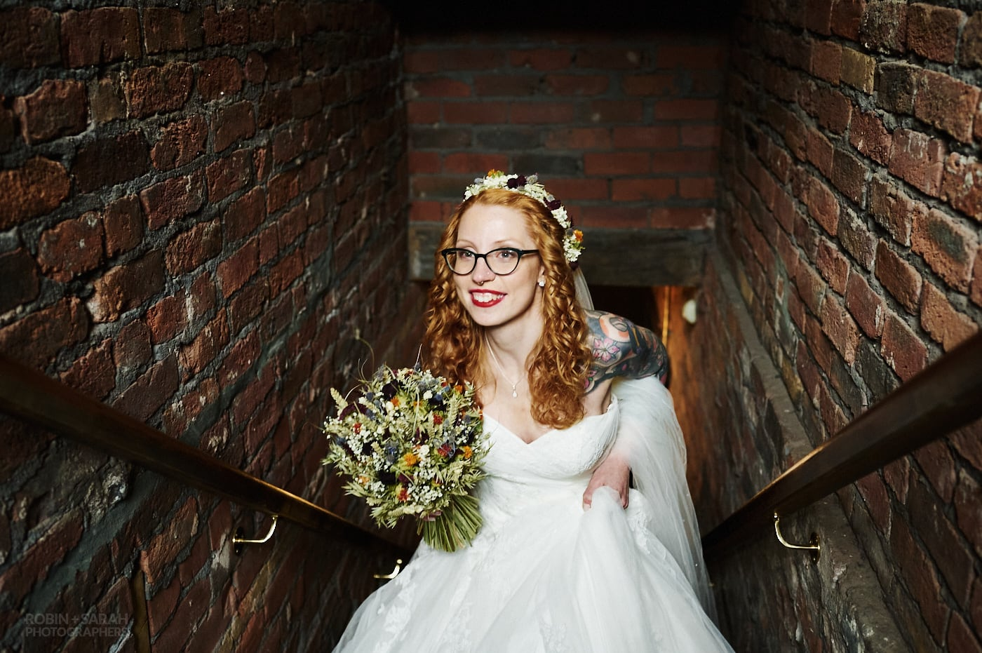 Bride with red hair and tattoos climbs staircase for wedding ceremony at The Chimney House