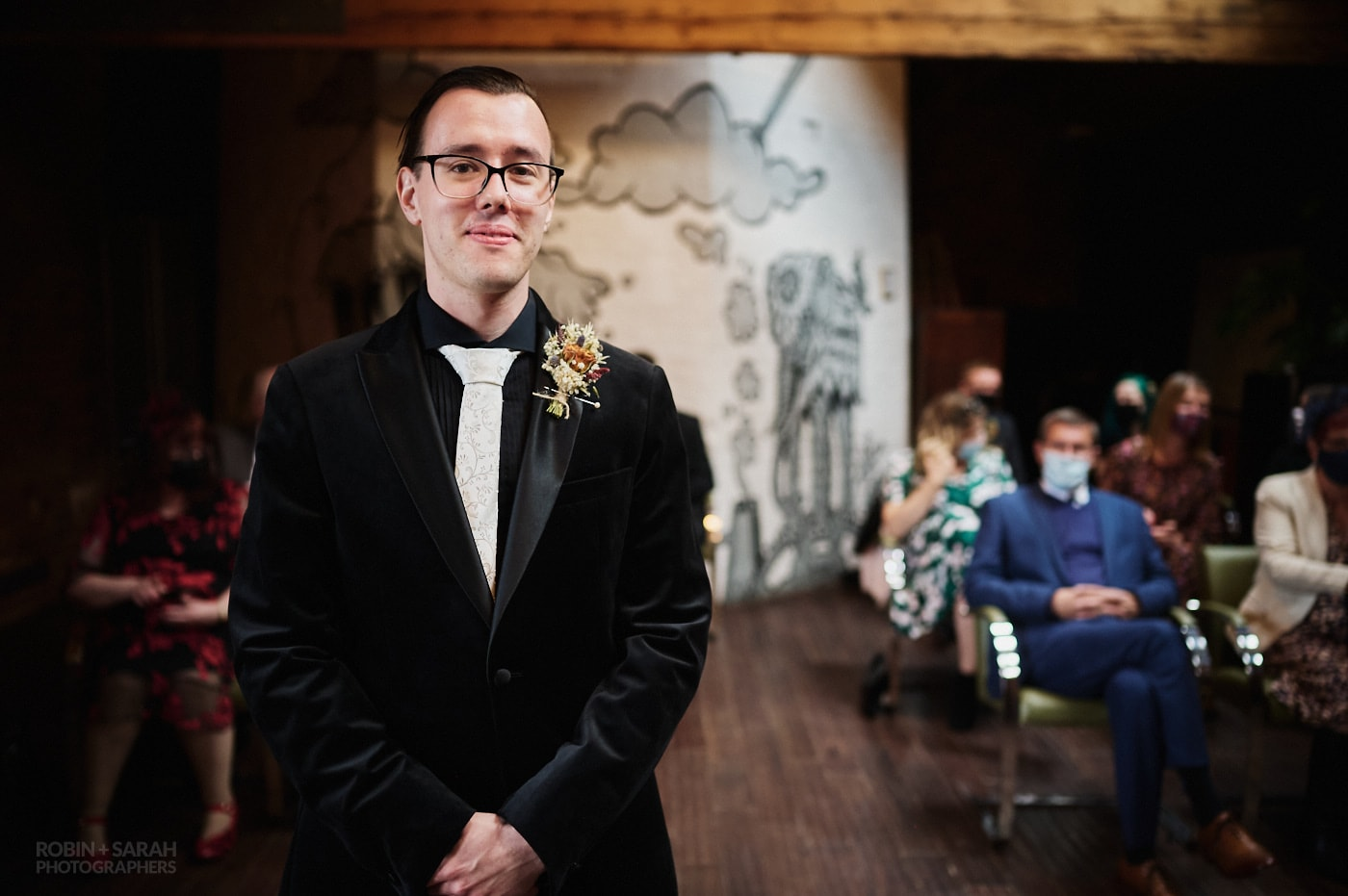 Groom waits for bride with guests watching