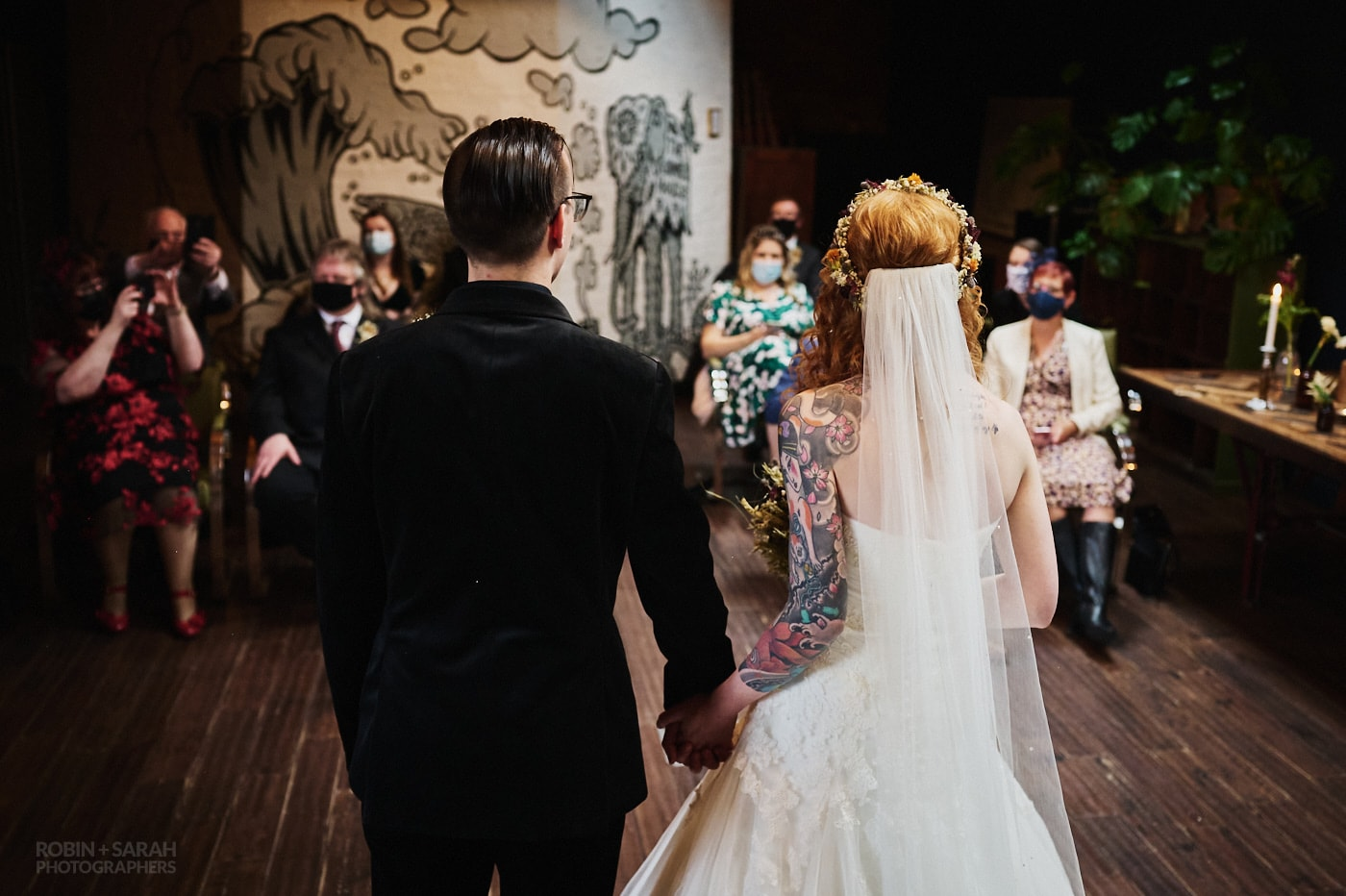 Newly married bride and groom turn to face their wedding guests