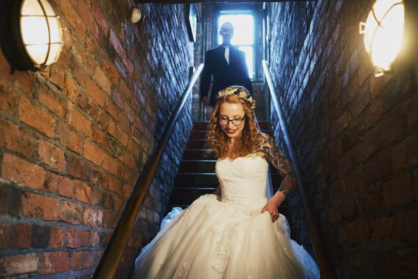 Bride holds her wedding dress as she descends staircase in The Chimney House wedding venue, with groom following behind
