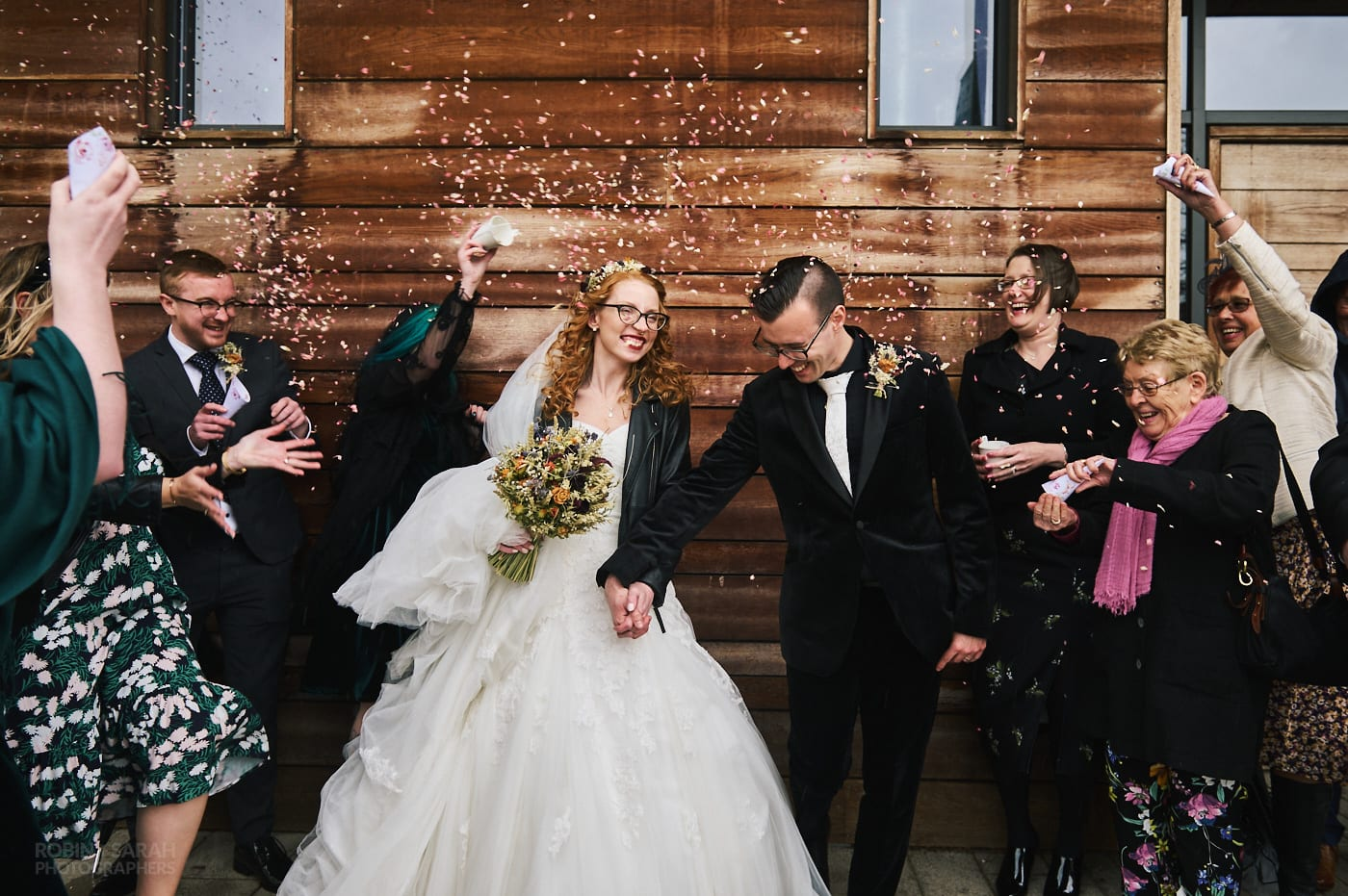 Wedding guests throw confetti over bride and groom outside building on Kelham Island in Sheffield