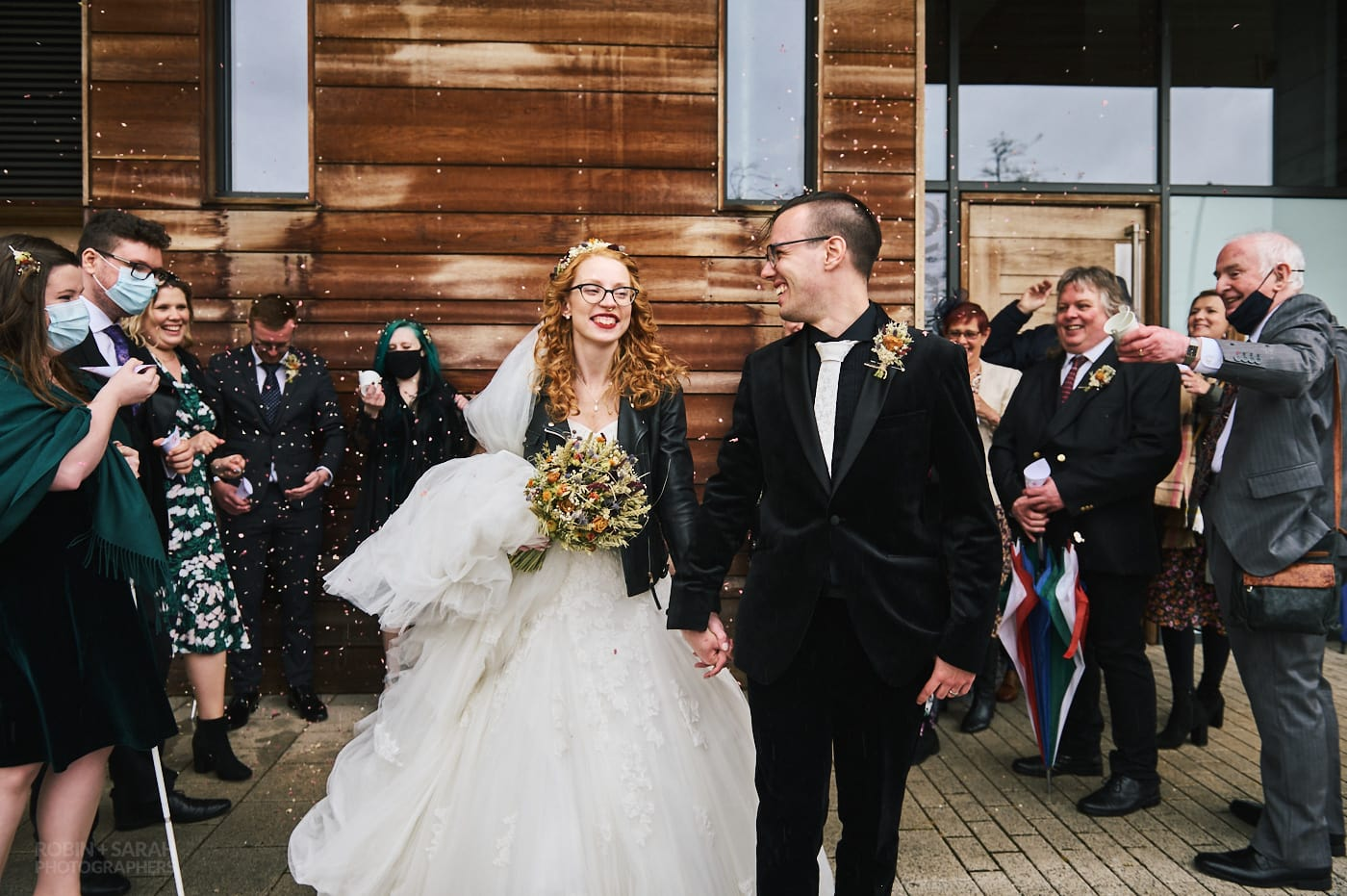 Bride and groom laughing as wedding guests throw confetti on Kelham Island