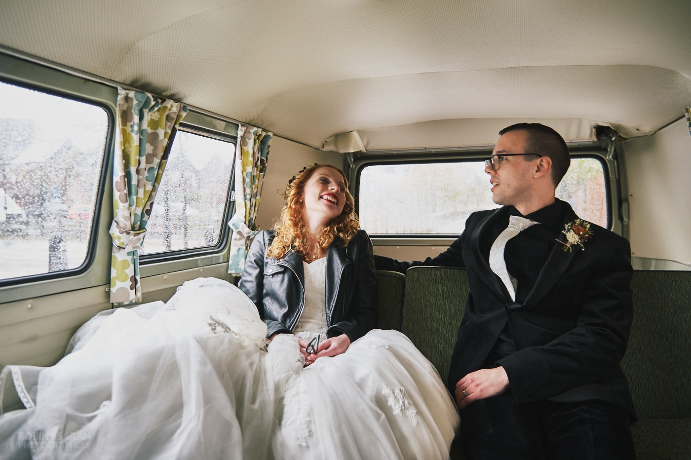 Bride and groom laughing together whilst in camper van