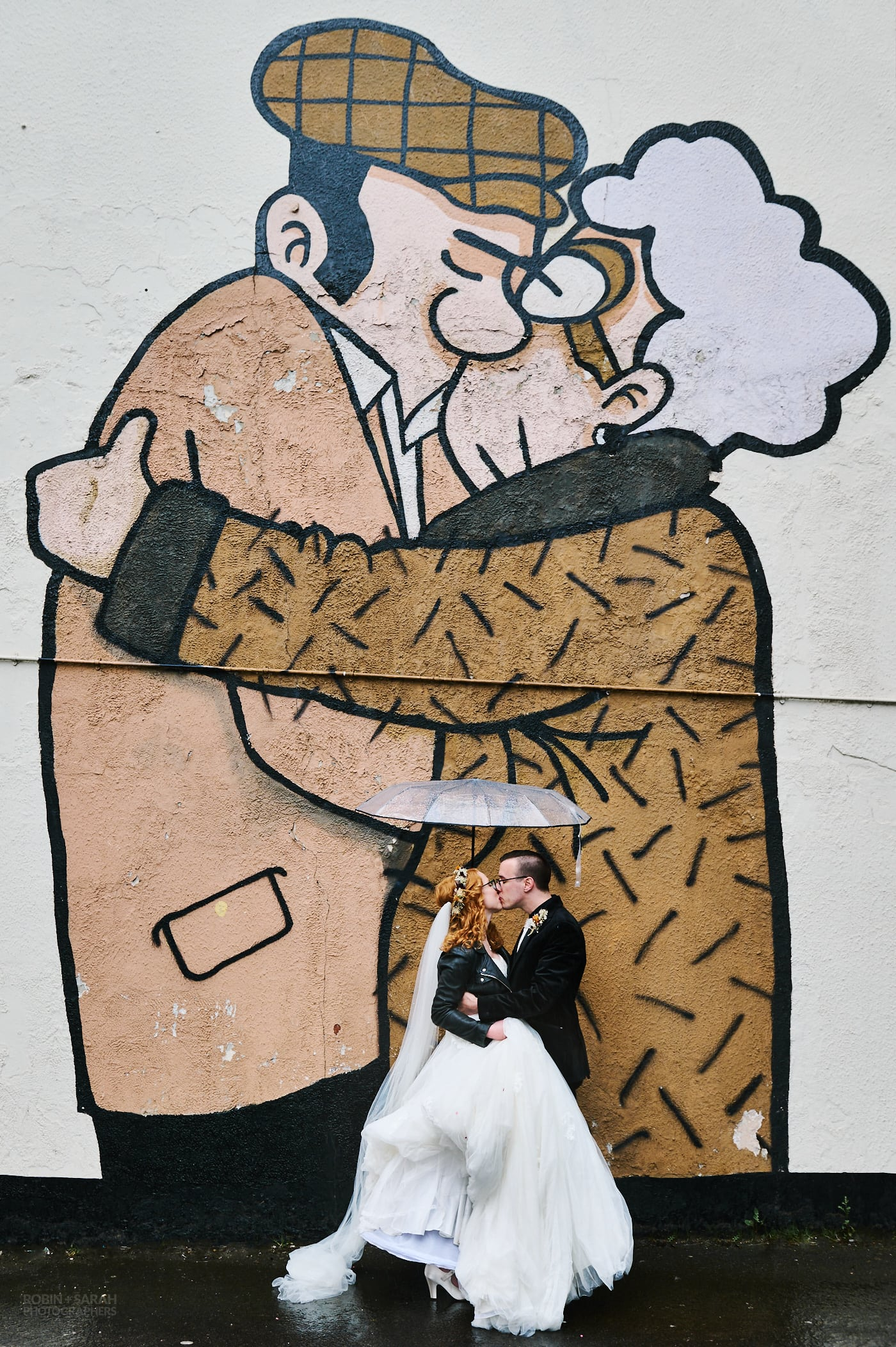 Newly married bride and groom kiss under umbrella in front of artwork 'The Snog' by Pete McKee in Sheffield