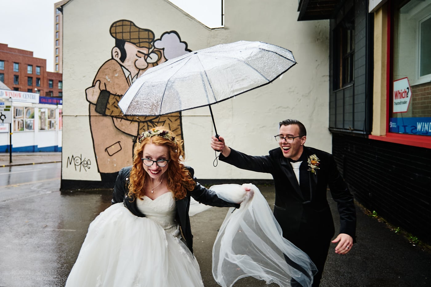 Bride and groom laughing as they run under umbrella with artwork 'The Snog' by Pete McKee in background