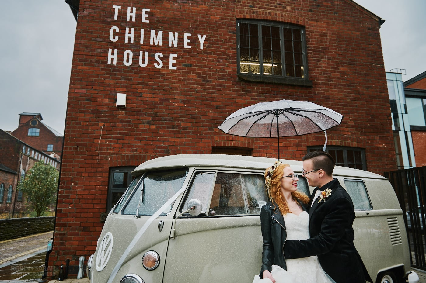 Bride and groom under umbrella outside The Chimney House wedding venue in Sheffield on a rainy day