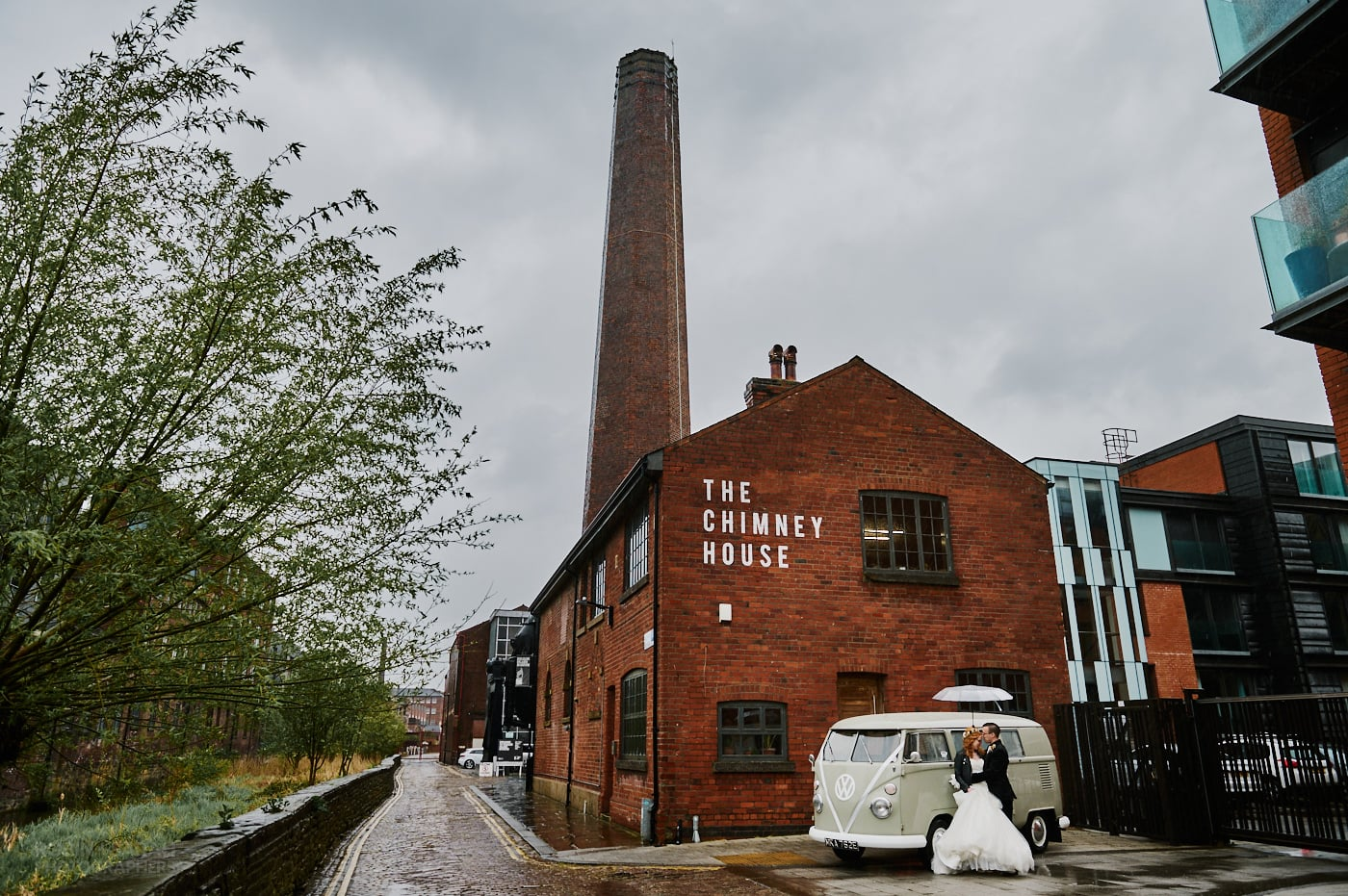 View of The Chimney House wedding venue in Sheffield with bride and groom standing together with camper van