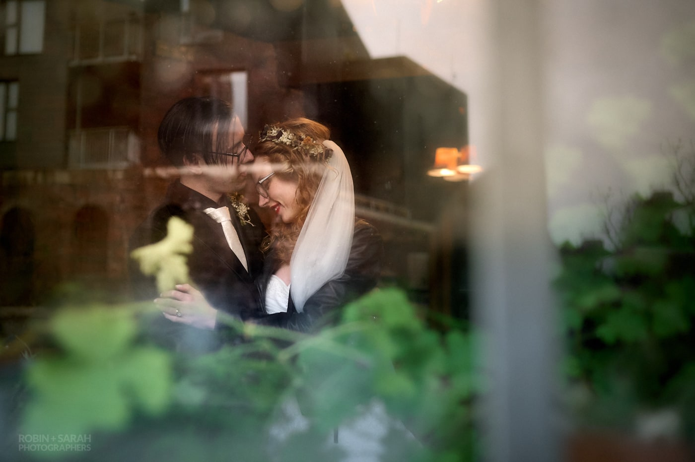 View through window of newly married couple enjoying quiet moment together in side The Chimney House wedding venue