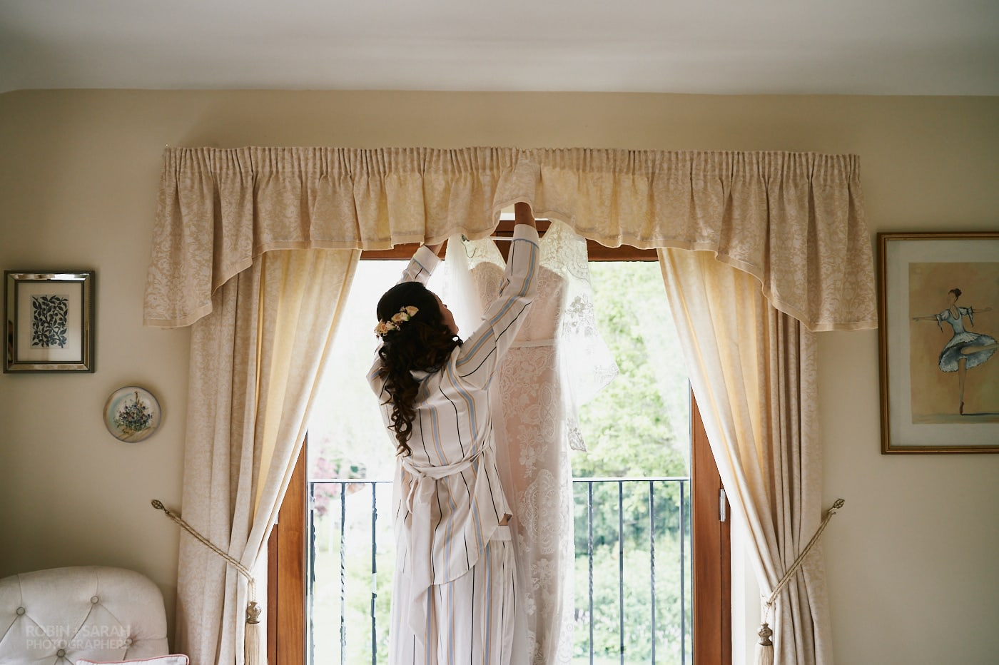 Bride hangs wedding dress on curtain rail