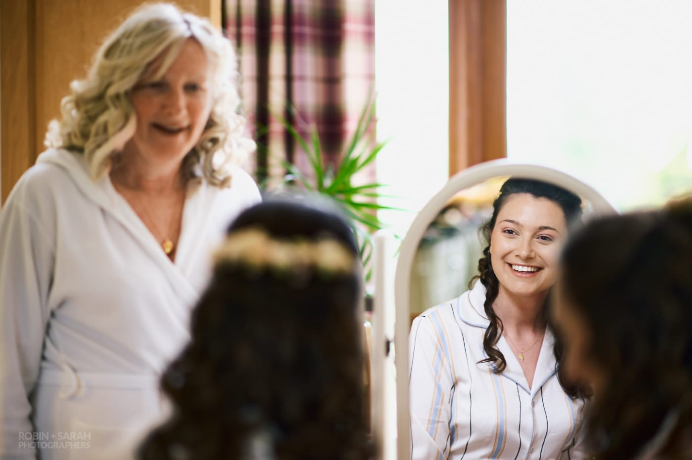 Bride smiling in mirror as she talks with mum