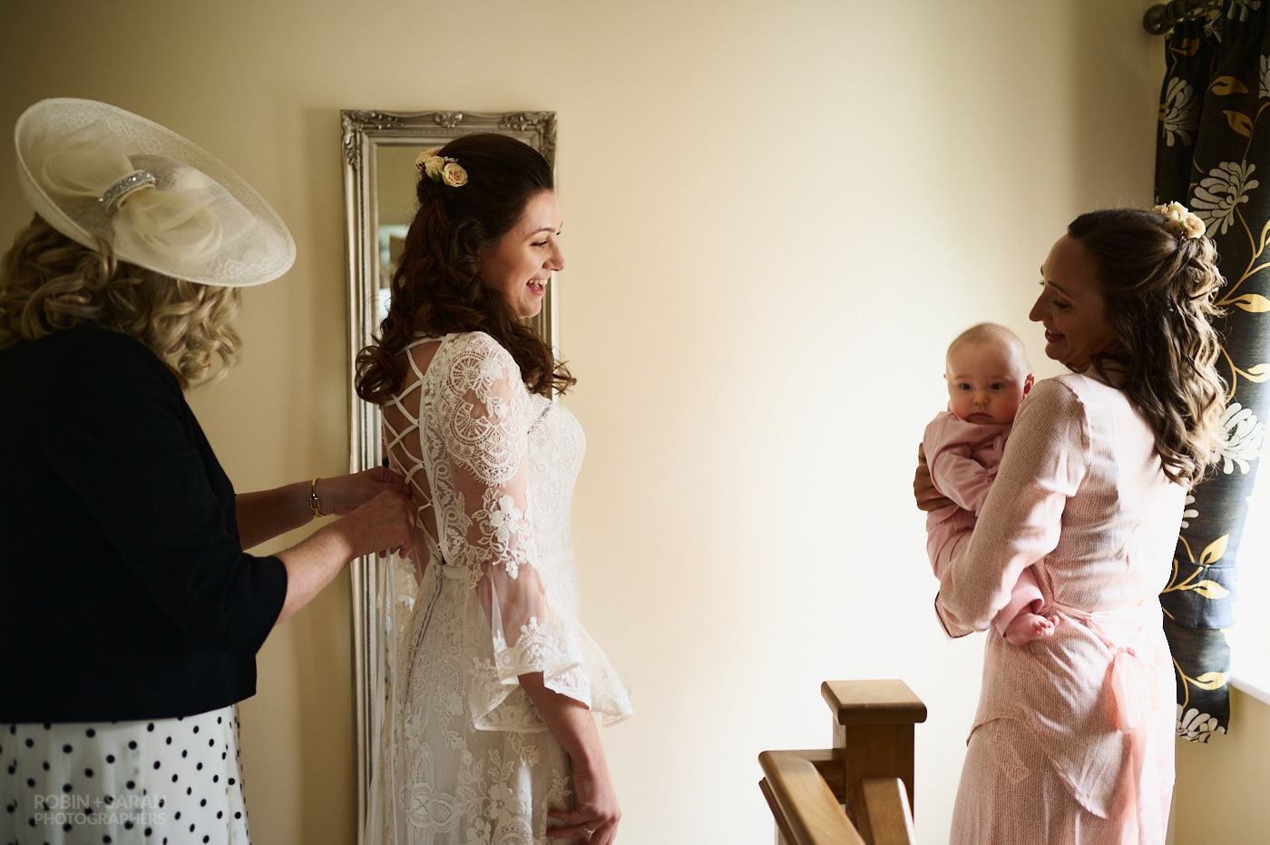 Bride chats with sister holding baby as mum fastens wedding dress