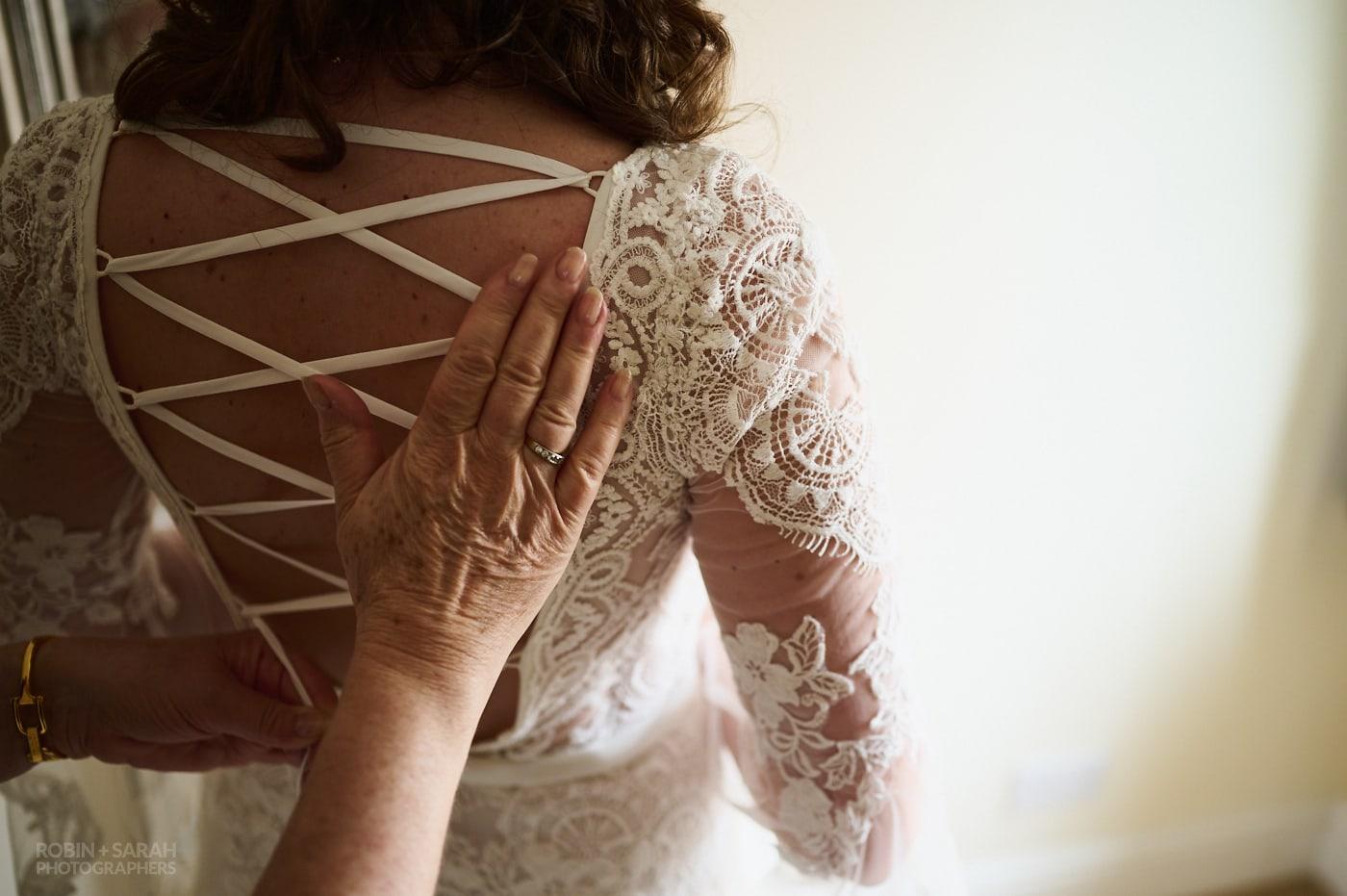 Bride's mum fastens daughter's wedding dress