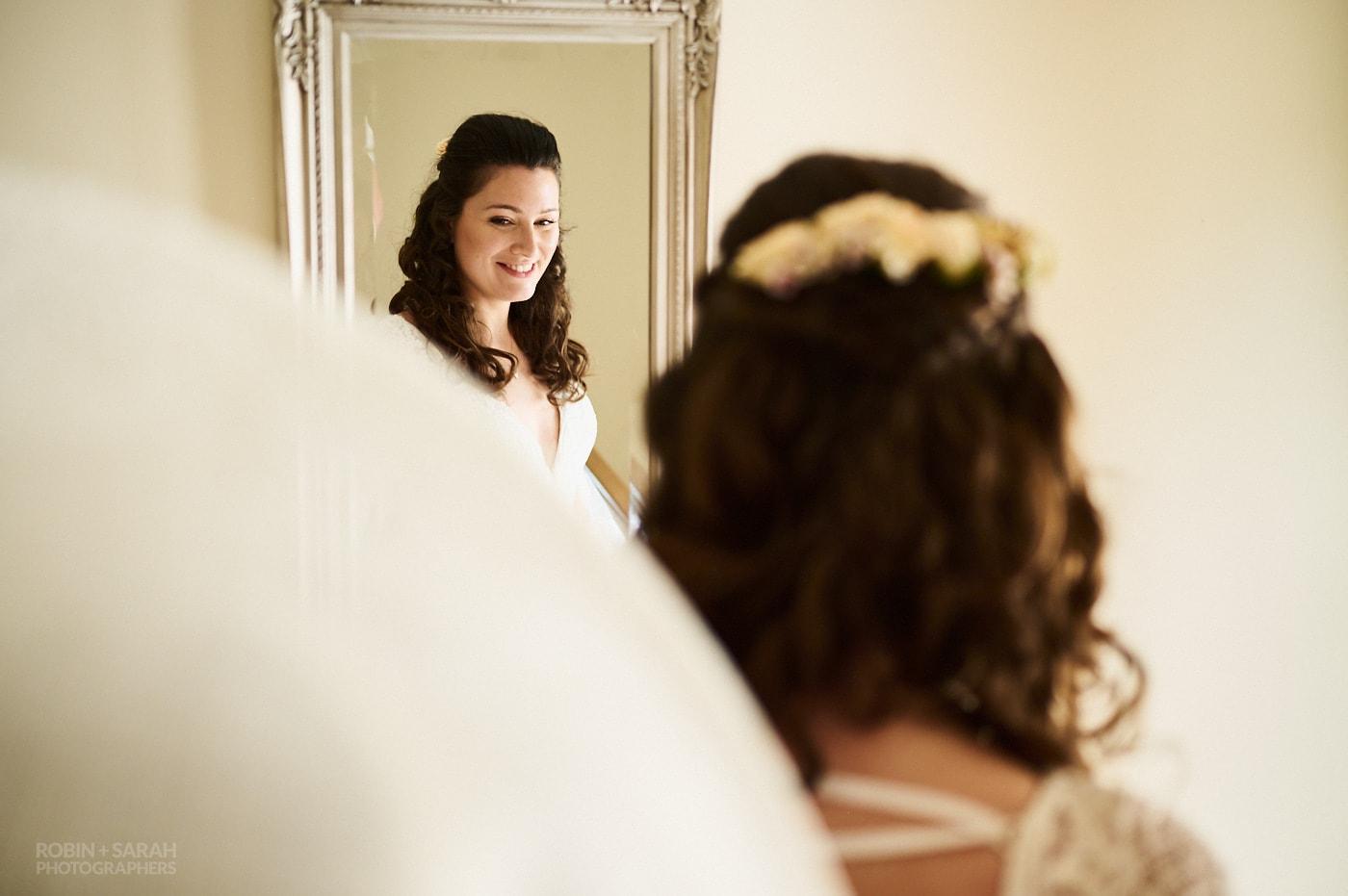 Bride smiling in mirror as mum in large hat fastens wedding dress