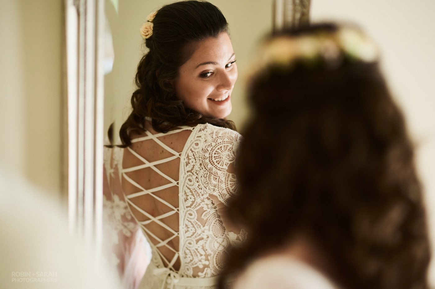 Bride looks at the bac of her wedding dress in mirror