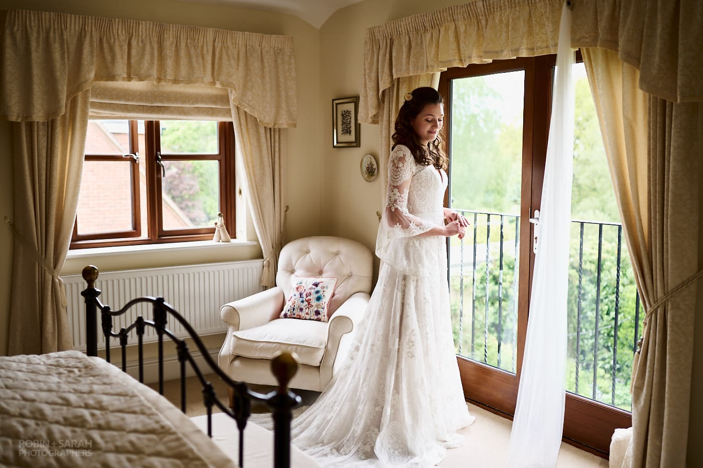 Portrait of beautiful bride in bedroom wearing a long wedding dress with lace sleeves