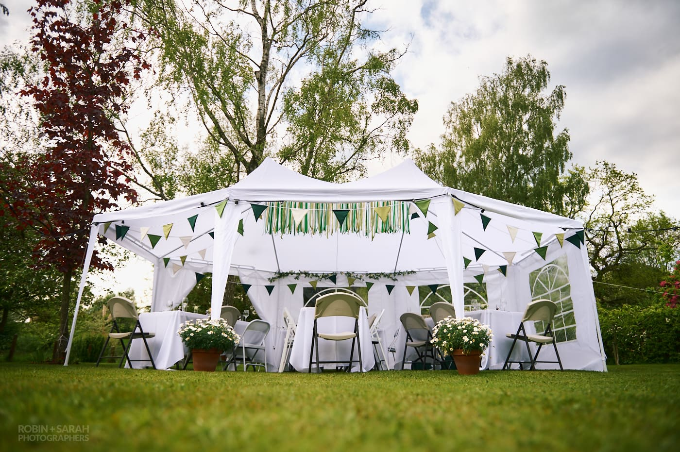 Small marquee set up for home garden wedding with green bunting