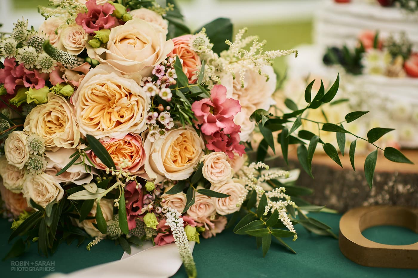 Bridal bouquet with peach and pink flowers resting on table