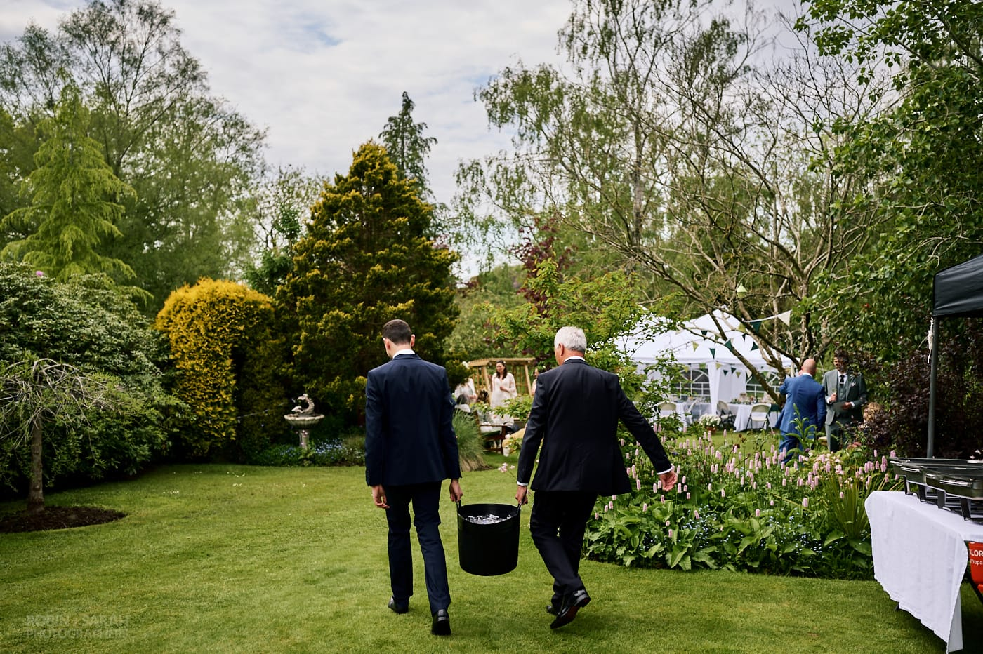 Two wedding guests carry bucket of iced drinks at home garden wedding reception