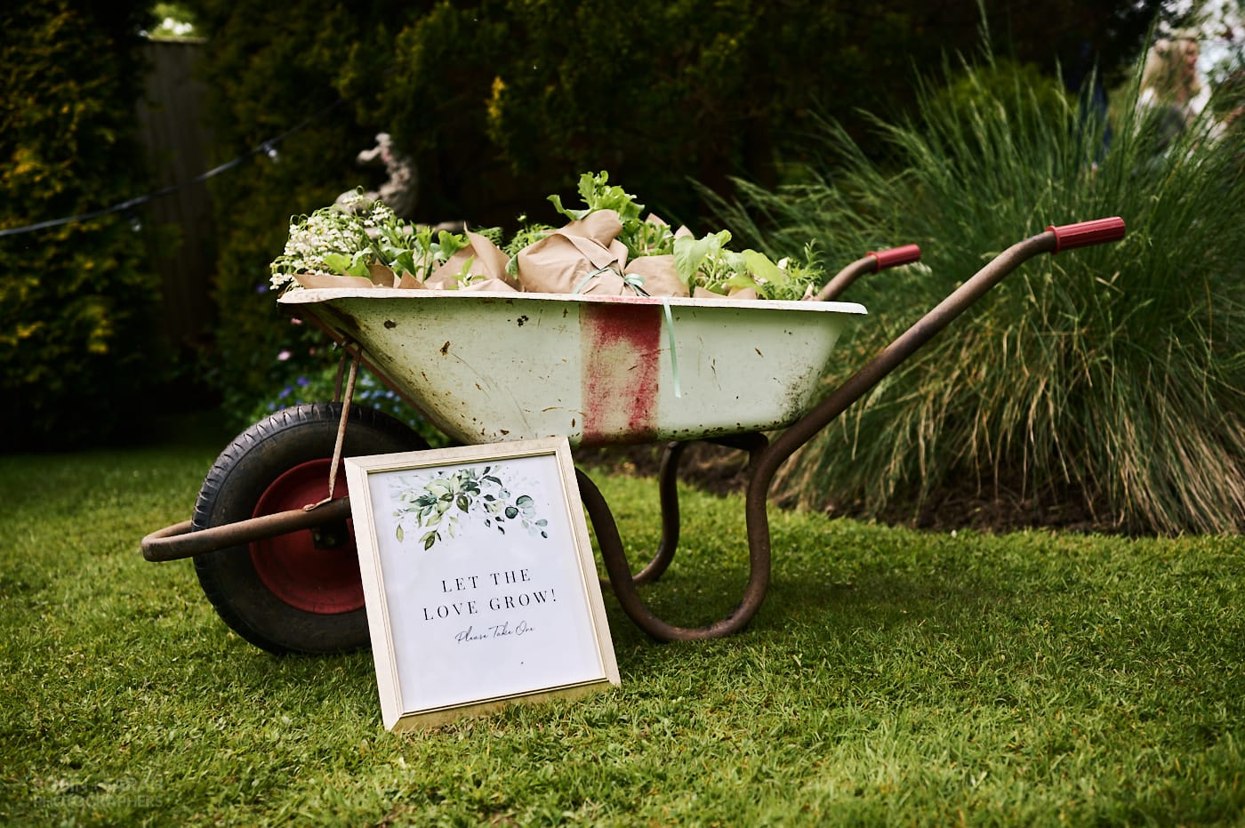 """Wheelbarrow full of potted plants for wedding guests to take and sign that reads """"let the love grow!"""""""
