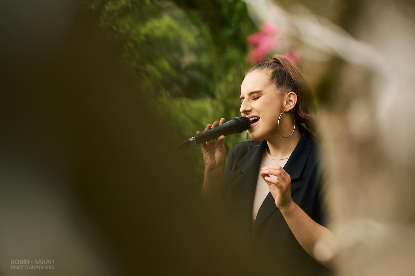 Vocalist singing at small garden wedding reception