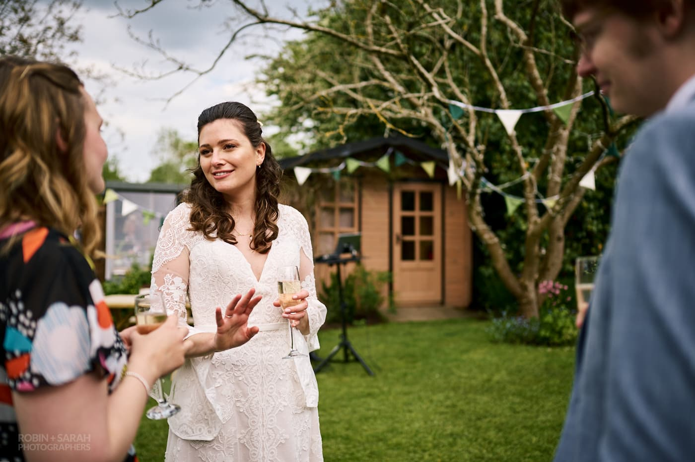 Bride chats with guests at home garden wedding