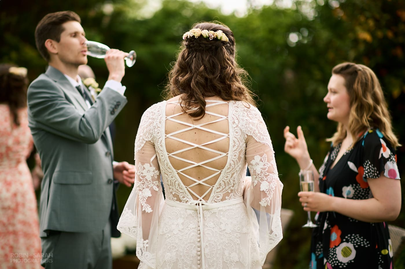 Back of bride's wedding dress on show as she chats to guests