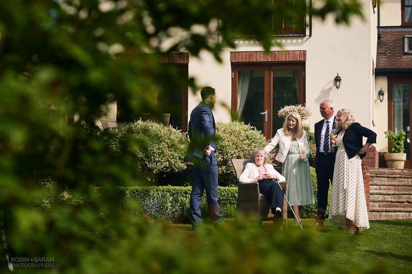 Wedding guests stand around elderly lady at small garden wedding reception