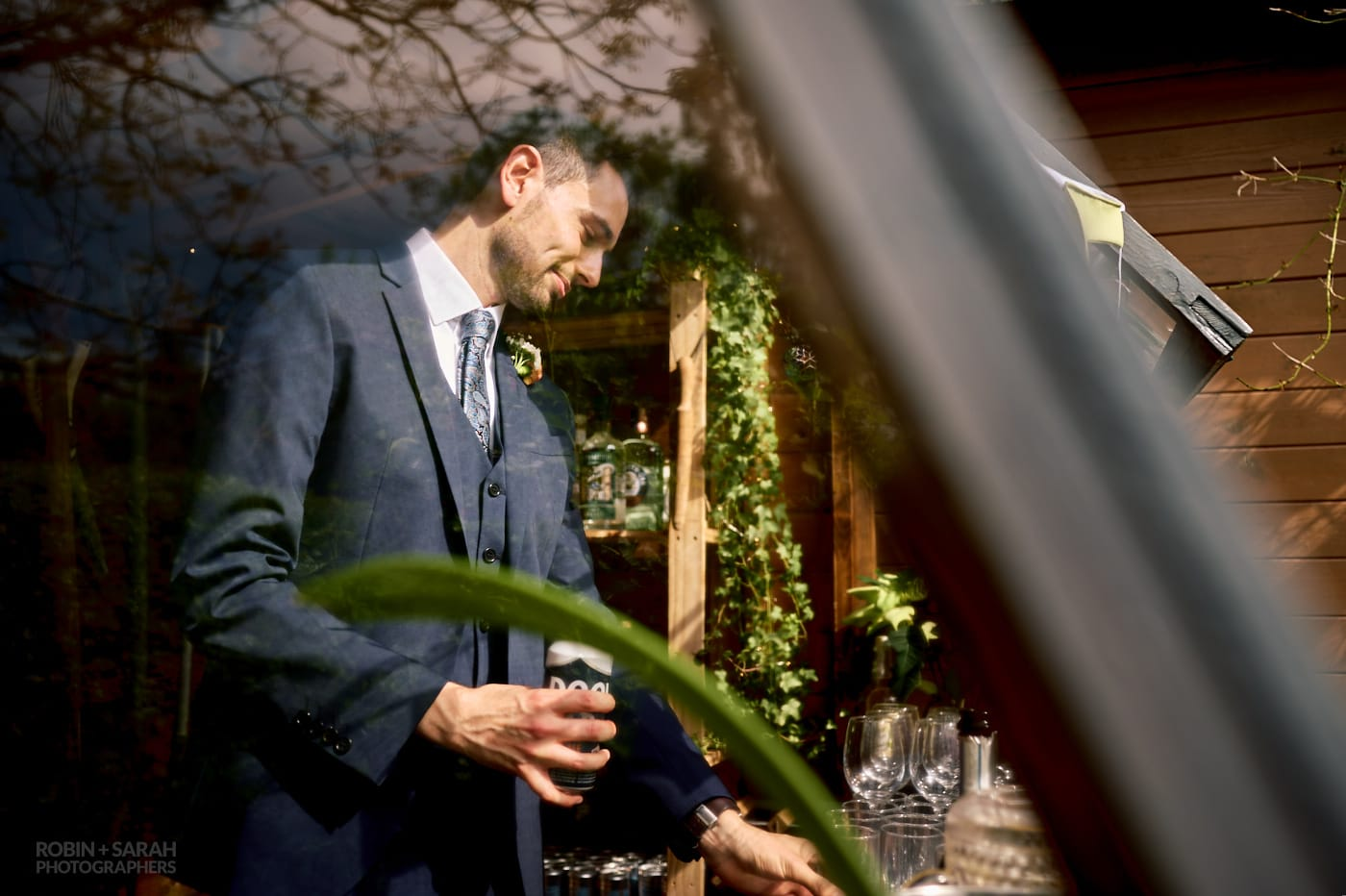 Wedding guests pours himself a drink in makeshift bar