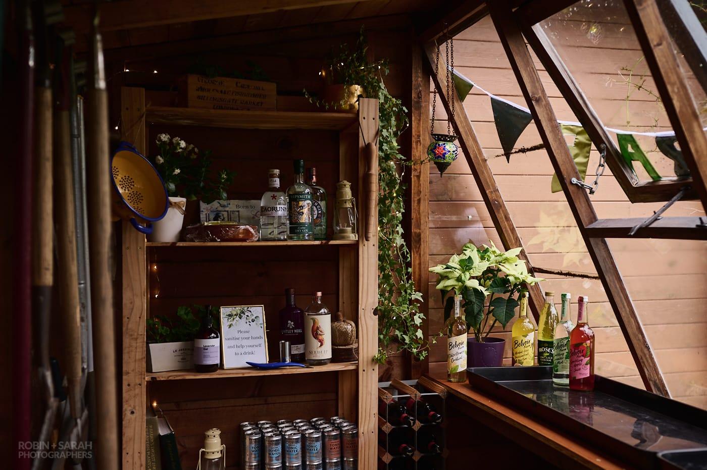 Makeshift bar set up in garden shed for home wedding
