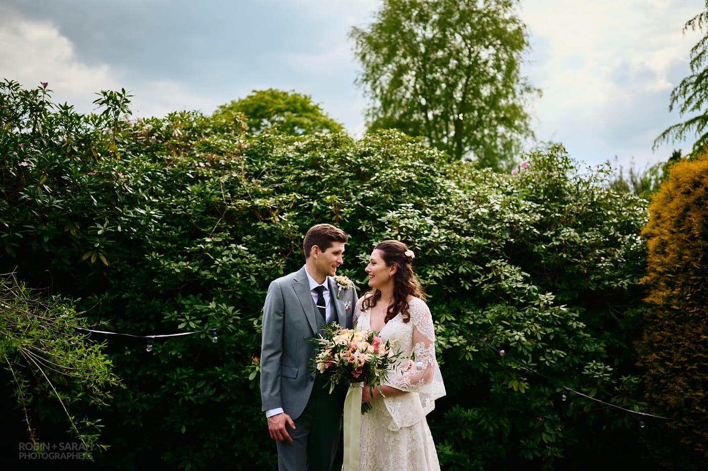Bride and groom chat to each other in front of large hedge