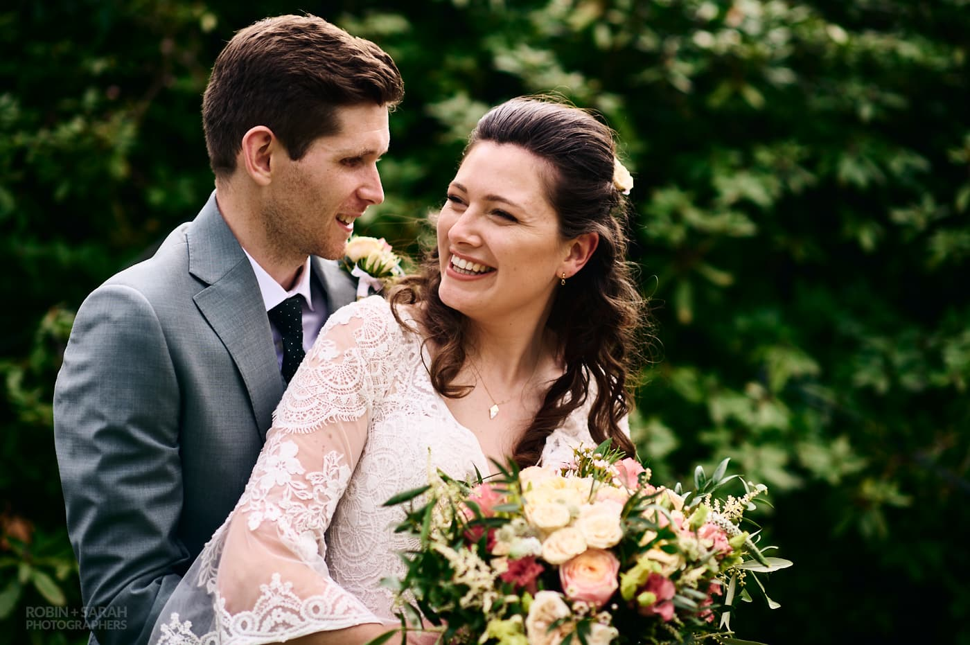 Bride and groom laughing together at garden wedding reception