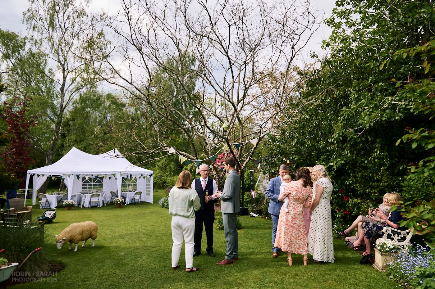 Small wedding reception taking place in home garden with small marquee