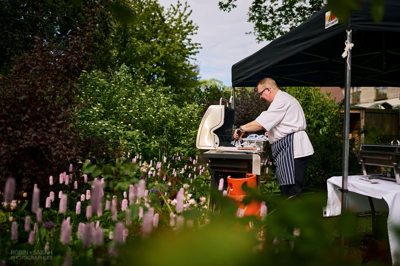 Chef prepares food at small garden wedding