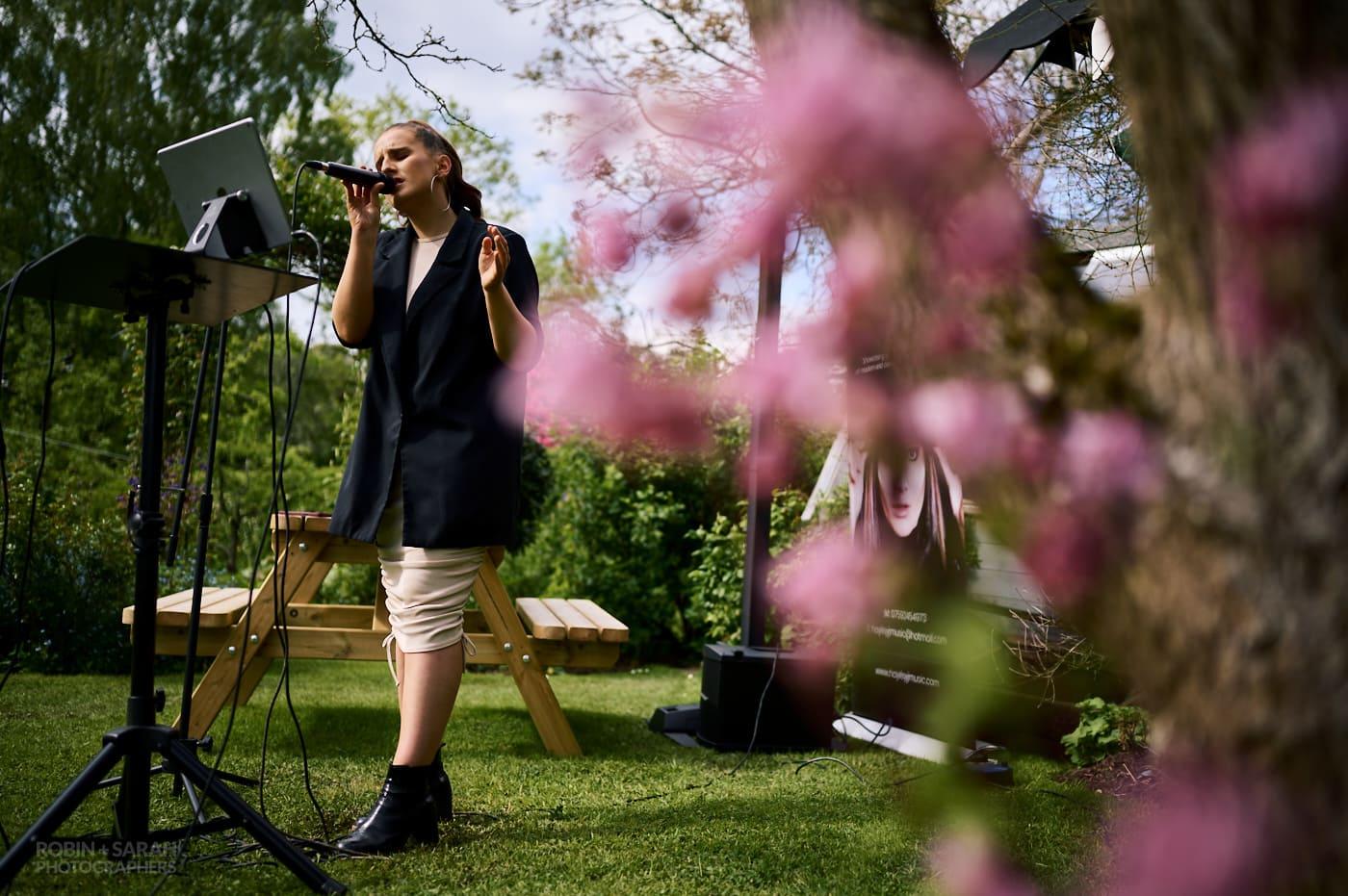 Female vocalist sings at garden wedding reception
