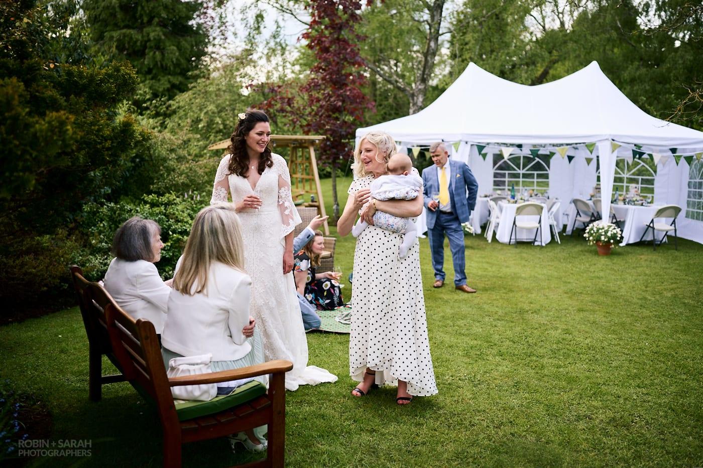 Bride and family relax at garden wedding reception