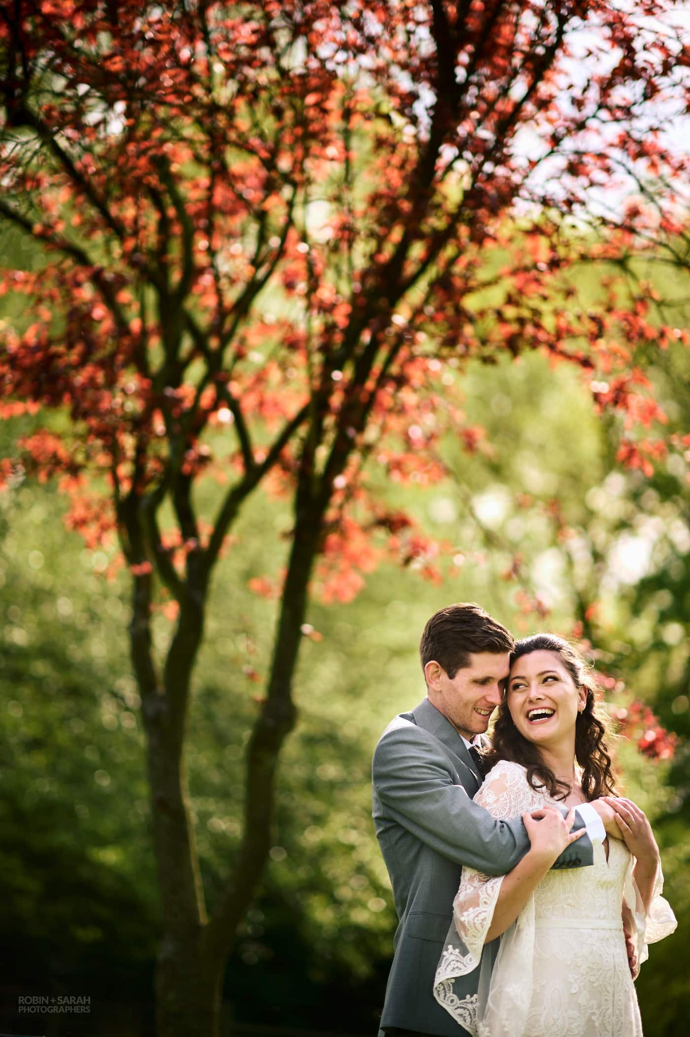 Groom holds bride as they relax at small garden wedding