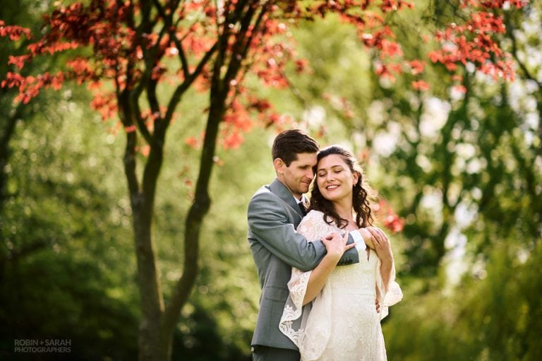 Groom holds bride as they share a quiet moment during garden wedding, with beautiful red tree in background