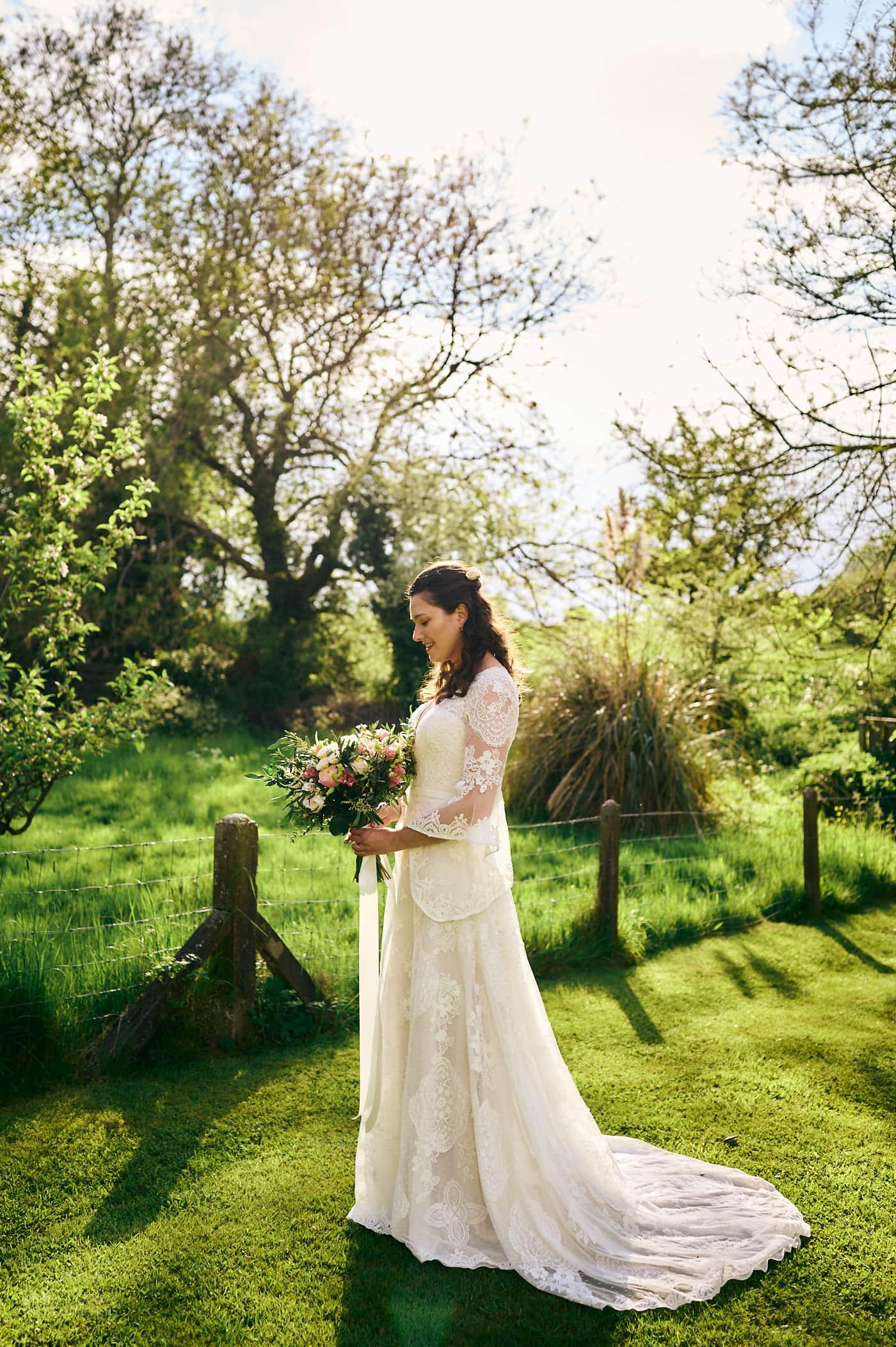 Bride in beautiful wedding dress holding bouquet stands in garden