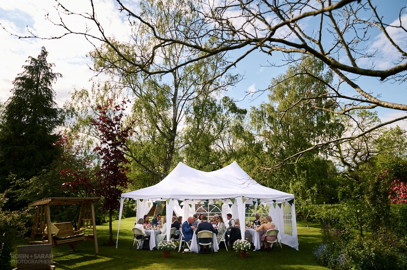 Small marquee set up for garden wedding with guests eating