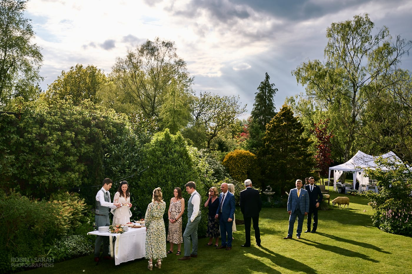 Wedding guests queue up to get pudding from bride and groom at small garden wedding