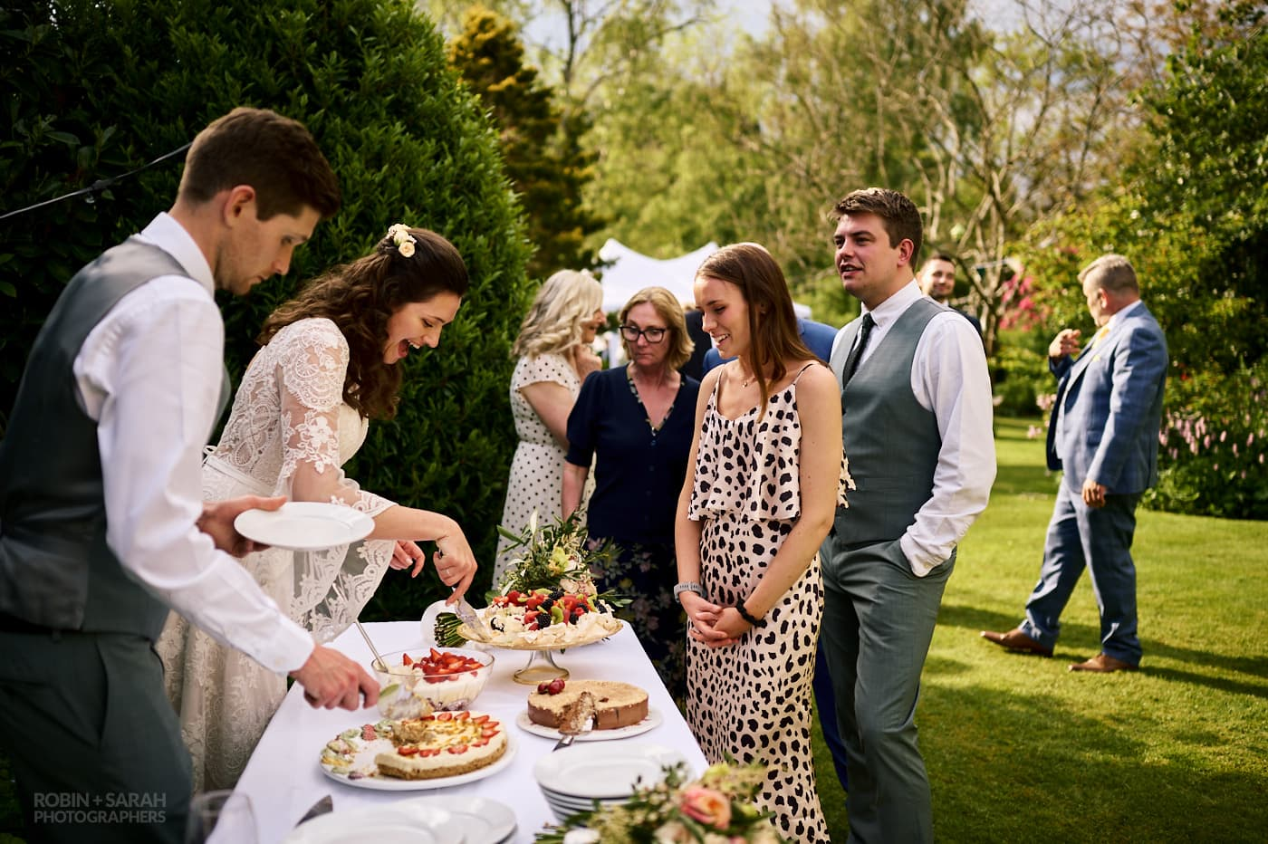 Bride and groom serve pudding to guests at small garden wedding