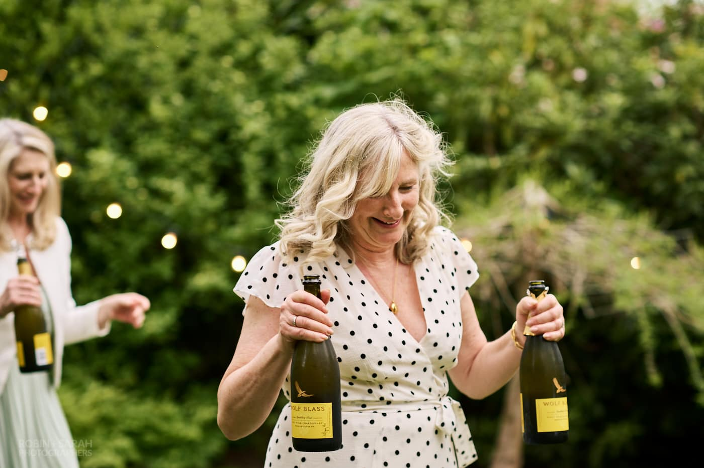 Guests carry bottles of Prosecco for wedding speeches in garden