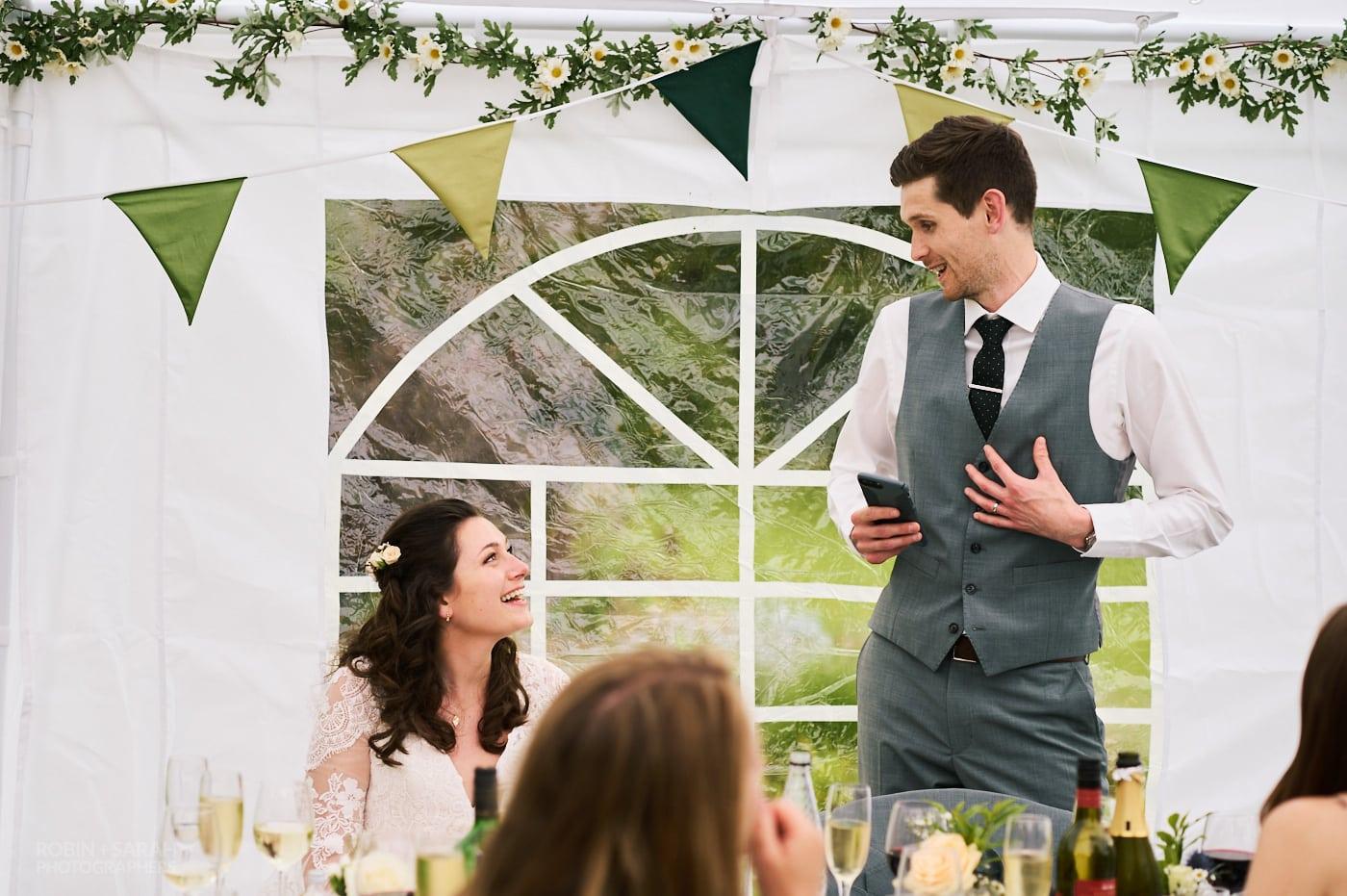 Groom delivers speech at small garden wedding