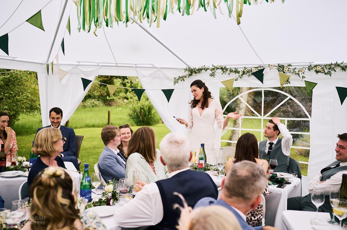 Bride gives speech in marquee at small garden wedding