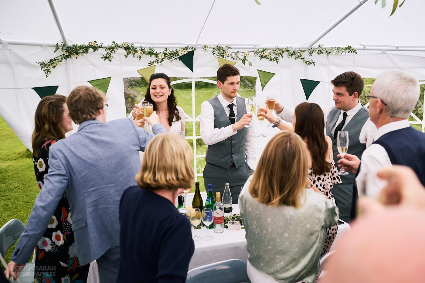 Bride and groom toast during speeches at small garden wedding